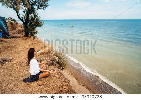 Attractive Woman In Summer Skirt And Shirt Sits On The Shore
