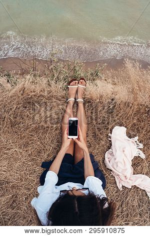 Beautiful Young Girl Sitting And Holding A Smartphone In Her Hands, Top View