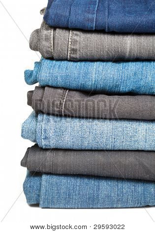 Stack of blue and black Jeans on white background