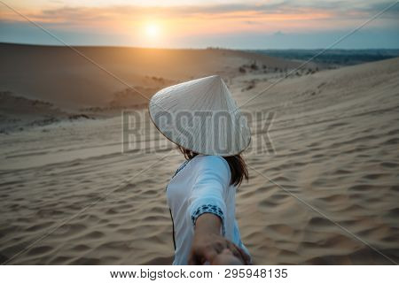 Man's hand holding hands of young woman traveler vietnamese traditional costume wearing Ao dai traveling into White Sand dunes at Mui ne in Vietnam at sunrise with beautiful sky poster