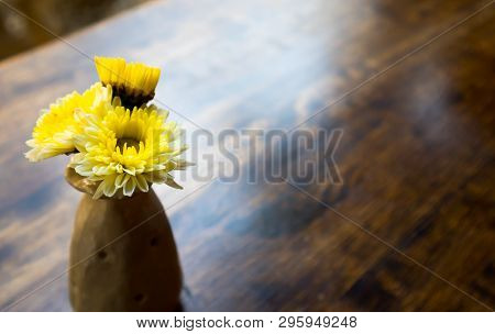 Yellow Flowers In A Ceramin Vase On The Dark Brown Wooden Table