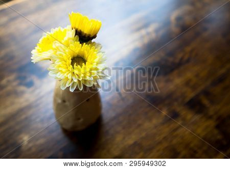 Yellow Flowers Stand In A Ceramin Vase On The Surface Of A Dark Brown Wooden Table