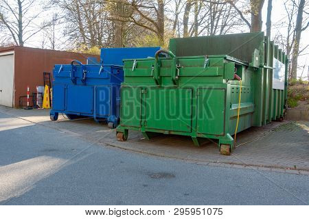 Two Garbage Compactors Are Standing In The Courtyard Of A Hospital