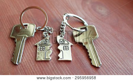 Pendant Of Key Ring In Shape Of House Divided In Two Parts On Wooden Background, Closeup View. Divid