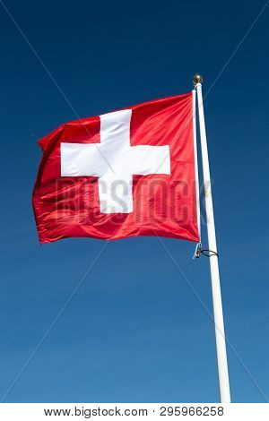 The Flag Of Switzerland With A Blue Sky.