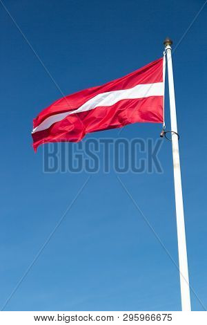The Flag Of Latvia Waving In The Wind With A Clear Blue Sky.