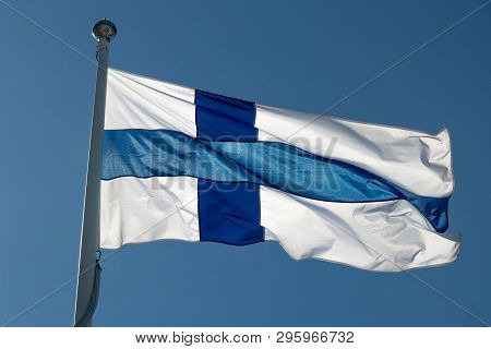 The Finnish Flag On A Flagpole Waving In The Wind With A Blue Sky.