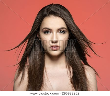 Woman with beauty long brown hair. Fashion model with long straight hair. Fashion model posing at studio. Pretty woman with long straight brown hair looking at camera. P