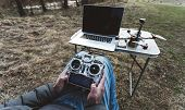 fpv drone pilot. A man sits in a chair with a remote from the FPV drone in front of a laptop and controls the copter. Racing aircraft. Racing copter. Mens hands with a racing copter remote control. poster