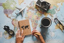 Top View Of Young Woman Planning Her Vacation Using World Map - Travel  Influencer Looking For The N