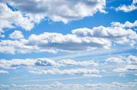 Blue sky background with white dramatic clouds and sunlight, vast sky background. Sky landscape scene, blue sky background with white clouds in the sky lit by sunlight. Natural sky background, sky sunny landscape