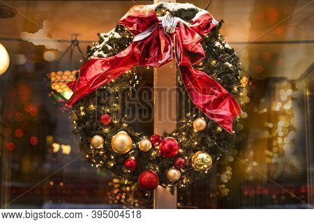 Christmas Wreath On The Cafe Door On A Festive Evening. Festive Decor Of A Street Cafe With Blurry L