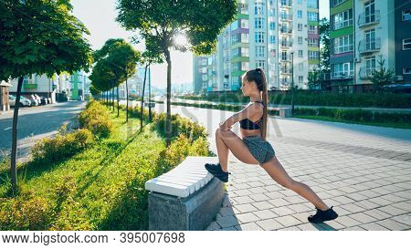 Side View Of Fitness Woman Wearing Sportswear Stretching Leg On Bench, Practicing Flexibility Exerci