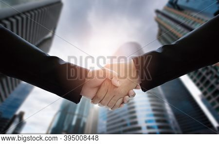 Close-up Of Business People Handshaking On Background Of Modern Building. Concepts Of Financial And