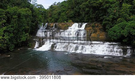 Aerial Top View Jungle Waterfall In A Tropical Forest Surrounded By Green Vegetation. Tinuy-an Falls