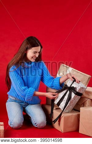 Girl Unties Bank On A Gift On A Red Background.