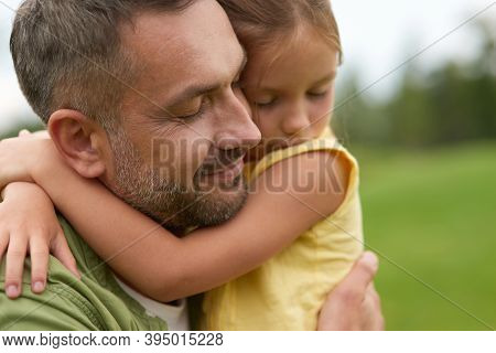 Close Up Of Happy Dad Holding His Lovely Little Daughter, Smiling, Standing With Eyes Closed While S