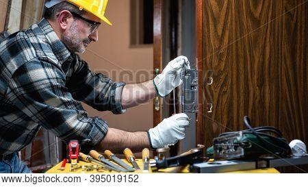 Carpenter At Work Repairs And Installs The Door Lock. Carpentry.