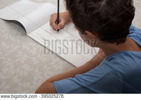 A Boy Sketching Out A Drawing Of A Seaside Town, Taken 13th Of August 2020 In Wool, Dorset, Uk