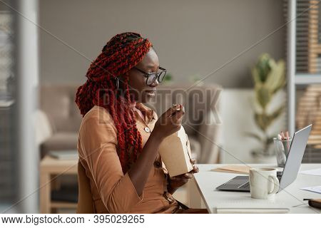 Side View Portrait Of Young African-american Woman Eating Takeout Lunch And Looking At Laptop Screen