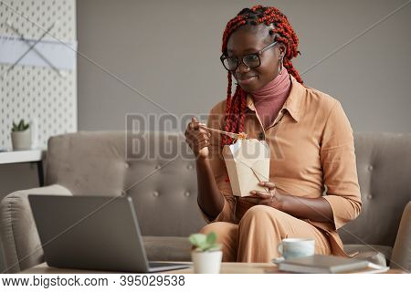 Portrait Of Young African-american Woman Eating Takeout Food And Looking At Laptop Screen While Rela