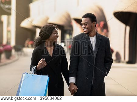 Man And Woman With Shopping Bags Talking And Smiling, Walking Down The Street After Black Friday And