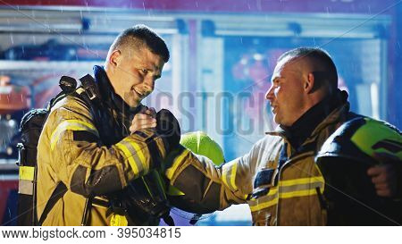 Portrait Of Two Young Firefighters On The Rain In Front Of Fire Engine In Full Uniform. Fire Dril. H