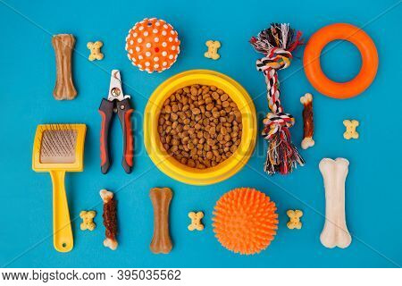 Set Of Accessories For The Dog On A Blue Background. Yellow Bowl, Ball, Goodies. Caring Concept. Can