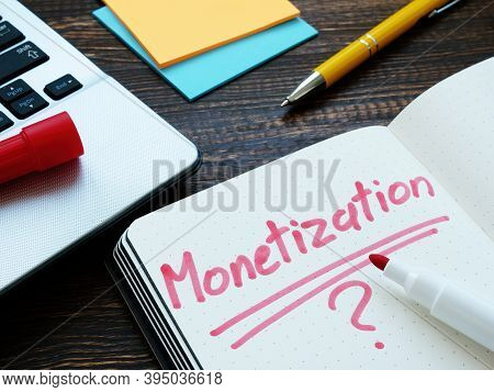 Monetization And Question Mark On Notepad Page And Notebook.