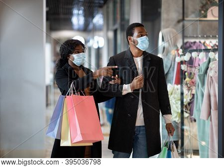 Black Friday And Covid-19 Quarantine. Millennial African American Male And Female In Coats And Medic