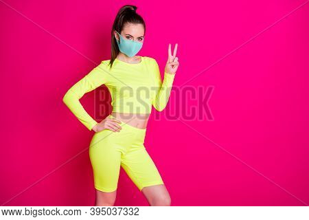 Photo Portrait Of Pretty Sportswoman Wearing Yellow Sportswear Mask Showing V-sign Gesture Isolated