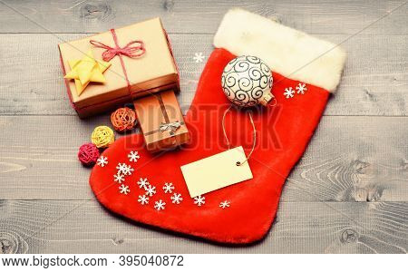 Stocking Stuffers Idea. Stocking With Christmas Gift Box. Christmas Sock Toned Wood Background Top V