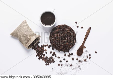White Coffee Cup , Coffee Beans Spilled Out Of The Bag, Wooden Spoon With Coffe On White Background.