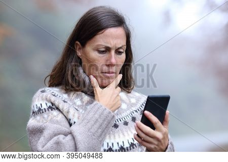 Worried Middle Age Woman Reading Smart Phone Message In Fall Season