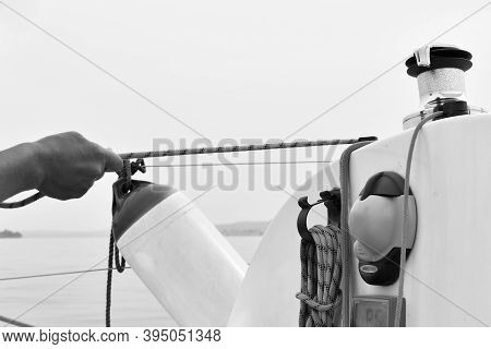 Close-up Of A Hand Pulling A Rope While The Sailboat Goes In Black And White