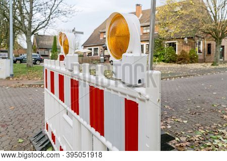 A Close Up Of A Plastic Red And White Roadworks Barrier Fence With Warning Hazard Lights Blocking Of