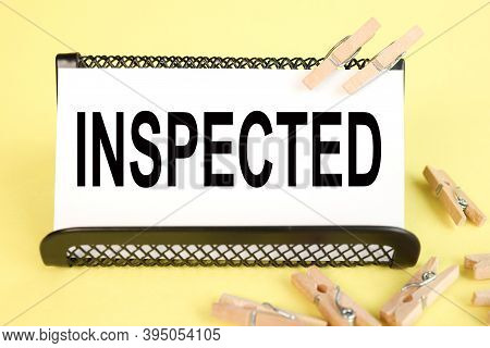 Inspected, Text On White Paper On A Yellow Background