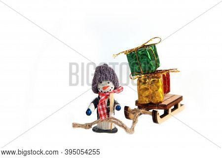 Snowman With Sledge Loaded With Bright Christmas Gifts Isolated On White Background. Winter Holiday