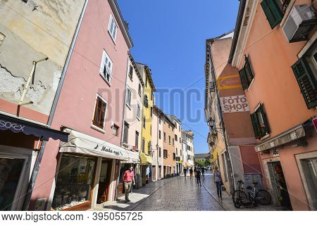 Rovinj, Croatia - April 1, 2020: Beautiful Narrow Street With Ancient Building Facades And Paving St