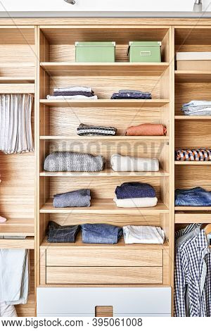 Modern Wardrobe With Clothes Hanging On Slide Out Racks And Folded On The Shelves. Modern Furniture