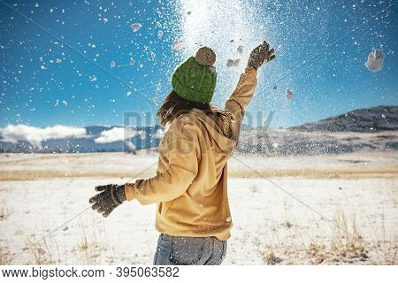 Happy Girl Is Having Fun And Tossing Snow In Mountains. First Snow Concept