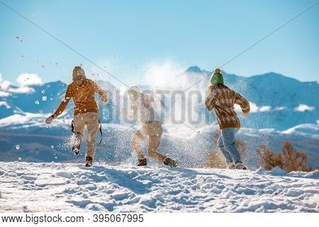 Three Young Happy Girls Friends Are Having Fun In Snow Fight In Mountains. First Snow And Winter Vac