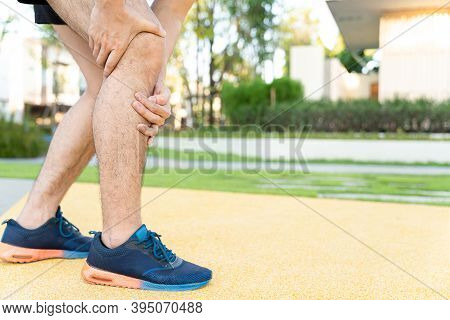 Male Runner Athlete Leg Injury And Pain. Hands Grab Painful Knee While Running In The Park.
