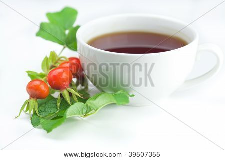 Cup Of Tea And Rosehip Berries With Leaves On White Background