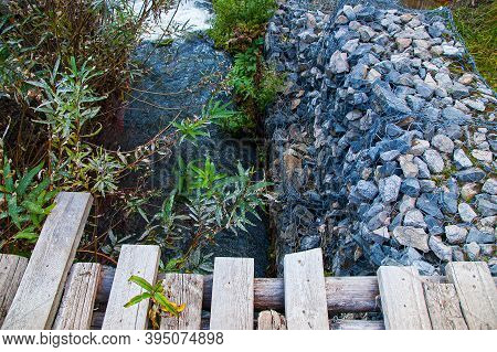 Strengthening The Gully Zone By The Stream With Stones And  Wooden Bridge  Flooring Of Planks In The