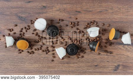 Espresso Coffee Capsules And Roasted Coffee Beans On Wooden Background Top View.