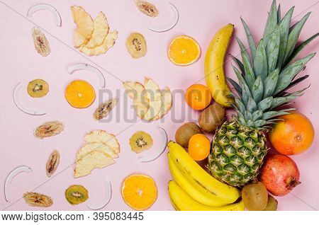 Tropical Fruits. Pineapple. Coconut, Orange, Bananas And Dry Fruit Chps On Pink Background. Food Con