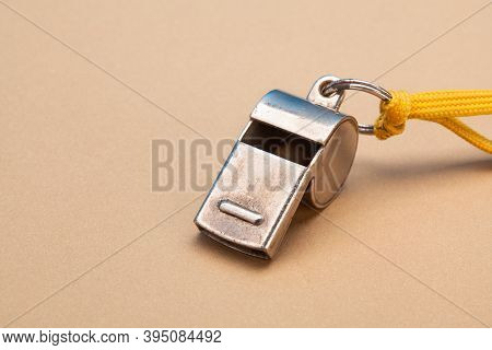 Vintage Silver Whistle On Soft Brown Paper Background. Referee Trainer Sport Competition Sound Instr
