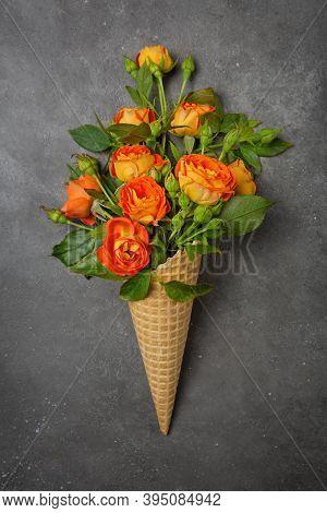 Fresh Yellow-orange Roses In A Waffle Cone On A Dark Grey Background. Copy Space, Flat Lay. Original