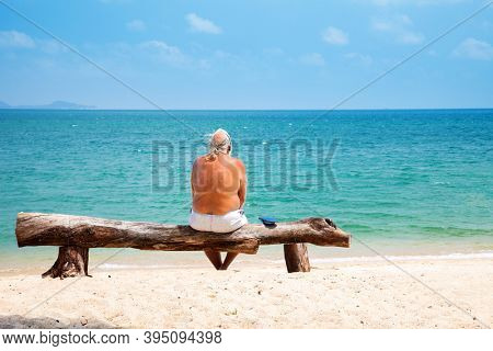 Old man sitting on the beach and looking to the sea